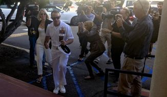 Navy Special Operations Chief Edward Gallagher, center right, walks with his wife, Andrea Gallagher as they arrive to military court on Naval Base San Diego, Tuesday, July 2, 2019, in San Diego. Jury deliberations continued Tuesday morning in the court-martial of the decorated Navy SEAL, who is accused of stabbing to death a wounded teenage Islamic State prisoner and wounding two civilians in Iraq in 2017. He has pleaded not guilty to murder and attempted murder, charges that carry a potential life sentence. (AP Photo/Julie Watson)
