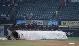 The grounds crew unrolls the tarp fefore a baseball game between the Detroit Tigers and the Chicago White Sox on Tuesday, July 2, 2019, in Chicago. (AP Photo/Jeff Haynes)