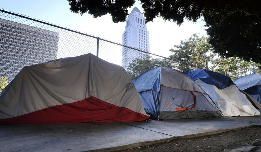 This Monday, July 1, 2019 photo shows Los Angeles City Hall behind a homeless tent encampment along a street in downtown Los Angeles. Los Angeles Mayor Eric Garcetti wants President Donald Trump to visit the city and work with him on the homeless crisis. The Democratic mayor made the public invitation during a radio interview Tuesday, July 2, 2109, after the Republican president called the homeless crisis in Los Angeles, San Francisco and other big cities disgraceful and threatened to intercede. (AP Photo/Richard Vogel)