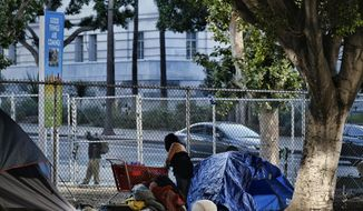 In this Monday, July 1, 2019 photo, a homeless woman moves her belongings in early morning from a street near Los Angeles City Hall (in the background) as crews prepared to clean the area. Los Angeles Mayor Eric Garcetti wants President Donald Trump to visit the city and work with him on the homeless crisis. The Democratic mayor made the public invitation during a radio interview Tuesday, July 2, 2109, after the Republican president called the homeless crisis in Los Angeles, San Francisco and other big cities disgraceful and threatened to intercede. (AP Photo/Richard Vogel)