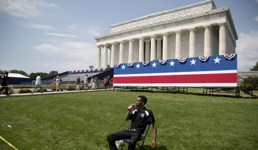 """An event staff member sits in the grass as workers set up for President Donald Trump's """"Salute to America"""" event honoring service branches on Independence Day at the Lincoln Memorial, Tuesday, July 2, 2019, in Washington. President Donald Trump is promising military tanks along with """"Incredible Flyovers & biggest ever Fireworks!"""" for the Fourth of July. (AP Photo/Andrew Harnik)"""