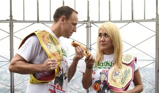 Eleven-time and defending men's champion Joey Chestnut, left, and defending women's champion Miki Sudo pose together during Nathan's Famous international Fourth of July hot dog eating contest weigh-in at the Empire State Building on Wednesday, July 3, 2019, in New York. (Photo by Evan Agostini/Invision/AP)