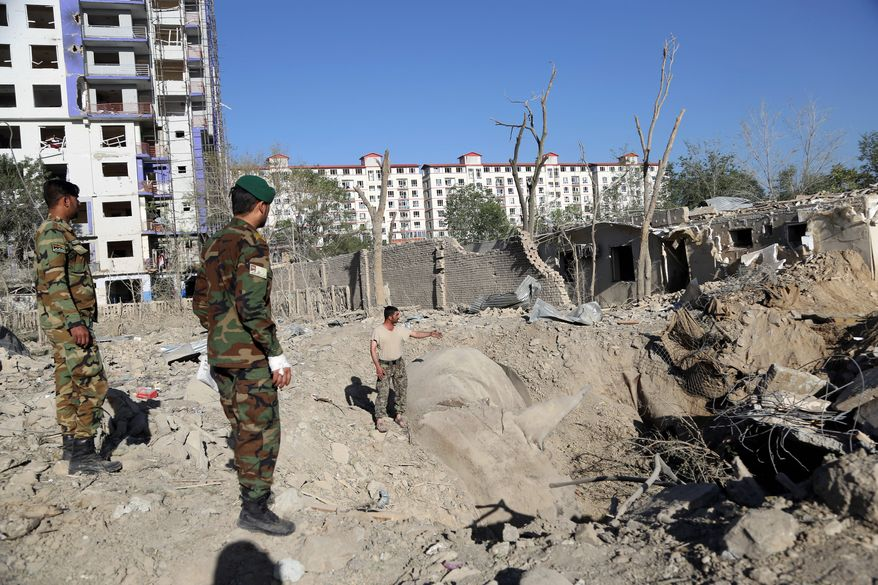 Afghan soldiers stand amid the aftermath of Monday's attack in Kabul, Afghanistan, Tuesday, July 2, 2019. The Taliban set off a powerful bomb in downtown Kabul on Monday, killing a several people and wounding more than a hundred, and sending a cloud of smoke billowing over the Afghan capital.  (AP Photo/Rahmat Gul)