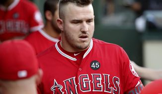 A black patch with the number 45 on it sits above the team logo as Los Angeles Angels' Mike Trout walks through the dugout in the first inning of a baseball game in Arlington, Texas, Tuesday, July 2, 2019. The entire team and staff wore the same patch honoring Tyler Skaggs. (AP Photo/Tony Gutierrez)