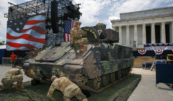 An Army soldier hops out of a Bradley Fighting Vehicle after moving it into place by the Lincoln Memorial, Wednesday, July 3, 2019, in Washington, ahead of planned Fourth of July festivities with President Donald Trump. (AP Photo/Jacquelyn Martin)