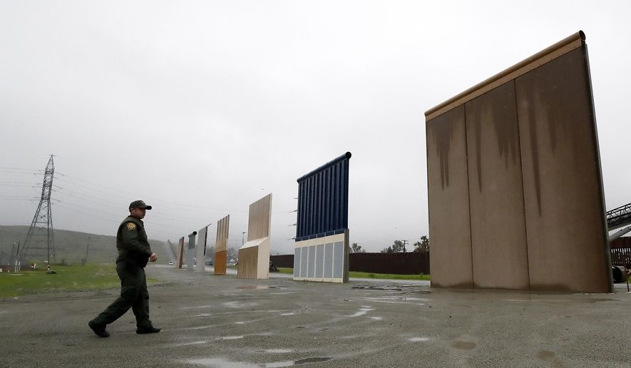 In this Feb. 5, 2019 file photo, Border Patrol agent Vincent Pirro walks towards prototypes for a border wall in San Diego.  (AP Photo/Gregory Bull, File) **FILE**