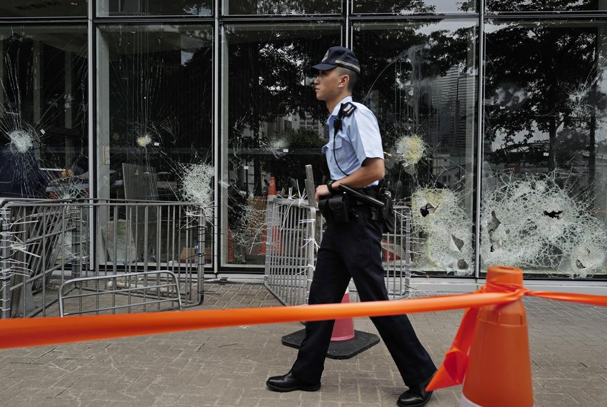 A police officer patrols outside Legislative Council building in Hong Kong, Tuesday, July 2, 2019. Hundreds of protesters swarmed into Hong Kong's legislature Monday night, defacing portraits of lawmakers and spray-painting pro-democracy slogans in the chamber before vacating it as riot police cleared surrounding streets with tear gas and then moved inside. (AP Photo/Vincent Yu)