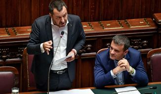 Italian Deputy Premier and Interior Minister Matteo Salvini, left, is flanked by the Minister For Agricultural Resources ,Gian Marco Centinaio, as he addresses the Lower Chamber in Rome, Wednesday, July 3, 3019. Italy's interior minister has told parliament that a German captain of a migrant rescue ship had no reason to force her ship to an Italian port. Matteo Salvini told the lower house of parliament on Wednesday that the migrants onboard the Sea-Watch ship would have been allowed to disembark anyway soon after captain Carola Rackete defied Italian orders to stay away. (Alessandro Di Meo/ANSA via AP)