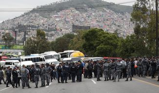 Uniformed federal police block the highway leading from Mexico City toward Pachuca, in Ecatepec, Wednesday, July 3, 2019. Hundreds of Mexican federal police are in open revolt Wednesday against plans to absorb them into the newly formed National Guard, saying their seniority, rank and benefits are not being recognized within the National Guard. (AP Photo/Rebecca Blackwell)