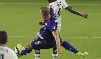 Orlando City's Robin Jansson (6) slides into Philadelphia Union's Fabrice-Jean Picault (9) during an MLS soccer match Wednesday, July 3, 2019, in Orlando, Fla. Jansson received a red card. (Stephen M. Dowell/Orlando Sentinel via AP)