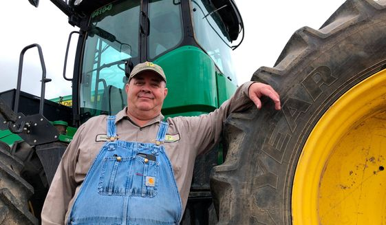 In this Thursday, June 20, 2019, photo, farmer Bernard Peterson leans on a tractor at his farm in Loretto, Ky. (AP Photo/Dylan Lovan) ** FILE **