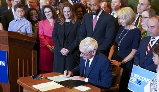 Wisconsin Gov. Tony Evers signs the budget Wednesday, July 3, 2019 at the State Capitol in Madison, Wis. Evers made 78 partial vetoes to the state budget passed by the Republican-controlled Legislature before signing it . (Steve Apps/Wisconsin State Journal via AP)