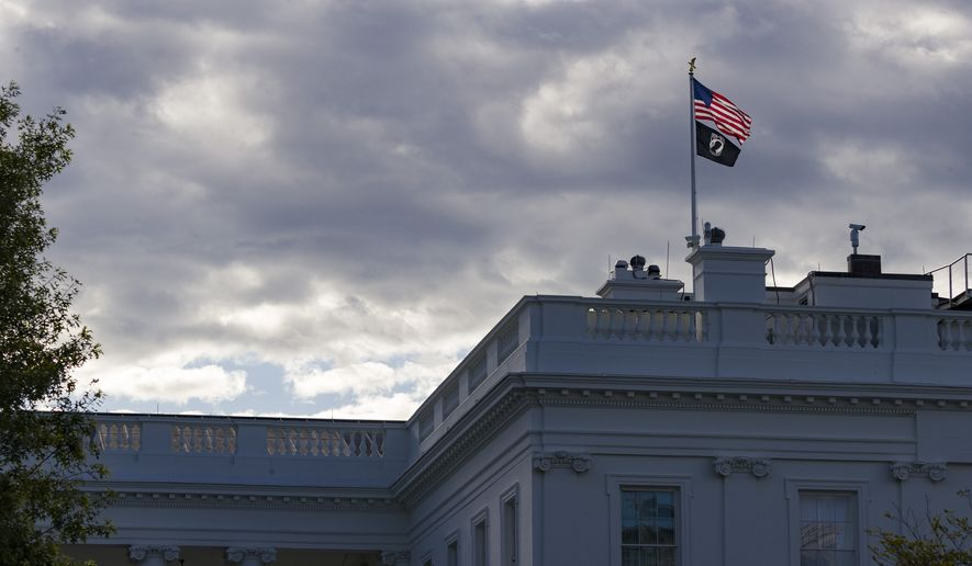 The U.S. flag and the POW-MIA flag fly over the White House on Flag Day, Friday, June 14, 2019, in Washington. (AP Photo/Alex Brandon)  ** FILE **