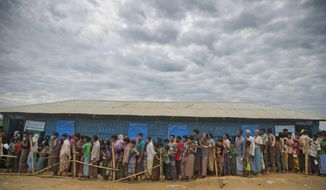 FILE - In this file photo dated Wednesday, Nov. 15, 2017, Rohingya Muslims, who crossed over from Myanmar into Bangladesh, wait in queues to receive aid at Kutupalong refugee camp in Ukhiya, Bangladesh.  The International Criminal Court prosecutor Fatou Bensouda said Thursday July 4, 2019, that she has filed a request with judges to open a formal investigation into crimes against humanity allegedly committed against Rohingya Muslims from Myanmar. (AP Photo/A.M. Ahad, FILE)