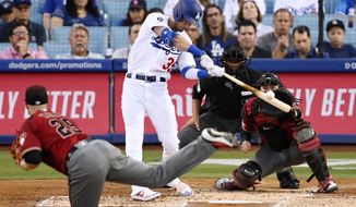 Los Angeles Dodgers' Cody Bellinger hits a solo home run off Arizona Diamondbacks starting pitcher Merrill Kelly, foreground, during the second inning of a baseball game Wednesday, July 3, 2019, in Los Angeles. (AP Photo/Mark J. Terrill)