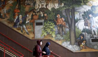 In this photo taken April 3, 2019, a pair of students walk past a historic mural that includes slaves and a dead Native American at George Washington High School in San Francisco. The San Fransisco school board unanimously voted Tuesday, June 25, 2019, to destroy a controversial mural displayed in a public high school. This is the latest move in recent times to remove New Deal-era art, now considered offensive. (Yalonda M. James/San Francisco Chronicle via AP)