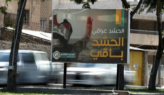 In this Tuesday, July 2, 2019, photo, motorists pass by a Popular Mobilization poster in Baghdad, Iraq. The Iraqi government's move to place Iranian-backed militias under the command of the armed forces is a political gamble by a prime minister increasingly caught in the middle of a dangerous rivalry between Iran and the U.S., the two main power brokers in Iraq. (AP Photo/Hadi Mizban)
