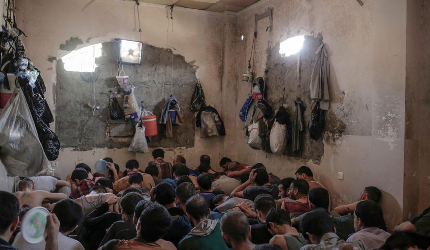 "FILE - In this Tuesday, July 18, 2017 file photo, Suspected Islamic State members sit inside a small room in a prison south of Mosul, Iraq. A leading international human rights organization is criticizing the Iraqi government for holding thousands of prisoners, including children, in degrading and ""inhuman"" conditions. (AP Photo/Bram Janssen, File)"