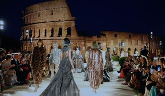 Models for Fendi present the Fall-Winter 2019-2020 collection 'The dawn of Romanity' during a couture runaway show in front of Rome's Colosseum,Thursday, Jul. 4, 2019. The show is meant to pay homage to fashion designer Karl Lagerfeld who passed away early this year at 85, ending his 54-year tenure with the luxury brand. (AP Photo/Domenico Stinellis)