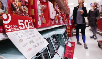 FILE - In this Nov. 23, 2018, file photo shoppers browse the aisles during a Black Friday sale at a Target store in Newport, Ky. (AP Photo/John Minchillo, File)