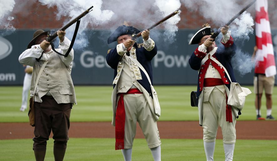 Members of a Revolutionary War re-enactment group fire a 13-gun salute during Independence Day festivities before a baseball game between the Philadelphia Phillies and the Atlanta Braves on Thursday, July 4, 2019, in Atlanta. (AP Photo/John Bazemore)