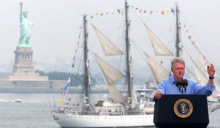 FILE - In this July 4, 2000 file photo, President Clinton speaks on the USS John F. Kennedy as a tall ship passes between him and the Statue of Liberty in New York Harbor during Independence Day celebrations in New York. (AP Photo/Ed Betz)