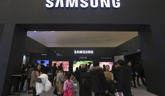 FILE - In this Jan. 30, 2019, file photo, visitors enter Samsung Electronics' booth during an industrial fair in Seoul, South Korea. Samsung Electronics Co. on Friday, July 5, 2019, says its operating profit for the last quarter likely fell more than 56% from a year earlier amid a weak market for memory chips. (AP Photo/Ahn Young-joon, File)