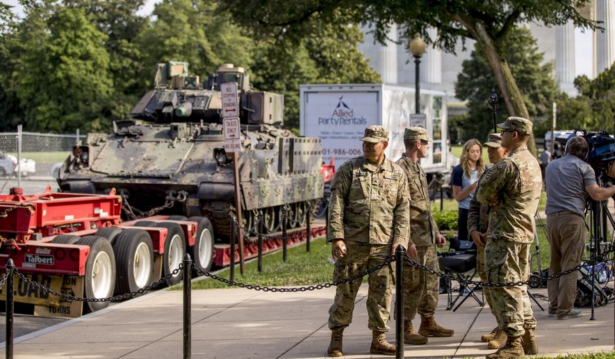 """Members of the military stand nearby one of two Bradley Fighting Vehicles parked nearby the Lincoln Memorial for President Donald Trump's 'Salute to America' event honoring service branches on Independence Day, Wednesday, July 3, 2019, in Washington. President Donald Trump is promising military tanks along with """"Incredible Flyovers & biggest ever Fireworks!"""" for the Fourth of July. (AP Photo/Andrew Harnik)"""