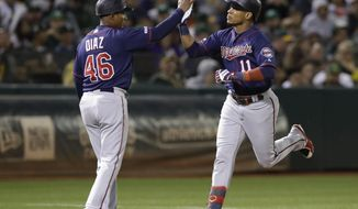 Minnesota Twins' Jorge Polanco, right, is congratulated by third base coach Tony Diaz (46) after hitting a home run off Oakland Athletics' Joakim Soria in the eighth inning of a baseball game Wednesday, July 3, 2019, in Oakland, Calif. (AP Photo/Ben Margot)