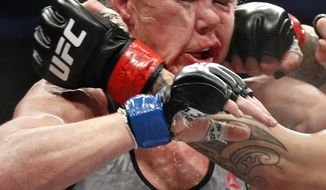 FILE - In this Dec. 30, 2017, file photo, Holly Holm gets hit in the face by Cris Cyborg, obscured at right, during a featherweight championship mixed martial arts bout at UFC 219 in Las Vegas. Holly Holm just can't stay away from the toughest challenges in her sports. The boxer-turned-mixed martial artist who has endured plenty of setbacks since she shocked Ronda Rousey will attempt to knock off dominant two-division champion Amanda Nunes on Saturday, July 6, 2019. (AP Photo/John Locher, File)