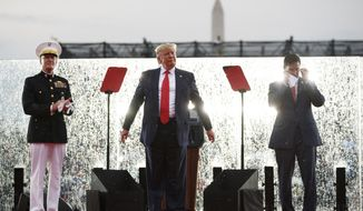 President Donald Trump, joined by Acting Secretary of Defense Mark Esper, right, and Joint Chiefs Chairman Gen. Joseph Dunford, left, stands on stage in the rain during an Independence Day celebration in front of the Lincoln Memorial, Thursday, July 4, 2019, in Washington. (AP Photo/Carolyn Kaster)