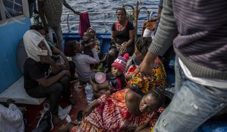 Migrants rest on their boat as it sails close to the Open Arms aid boat on Sunday June 30, 2019. A Spanish humanitarian group says its rescue ship spotted 40 dehydrated migrants at sea and their boat is now being escorted to the tiny Italian island of Lampedusa. Proactiva Open Arms spokeswoman Laura Lanuza told The Associated Press that three pregnant women and four children are among the passengers on the boat being escorted by Italy's coast guard Sunday. (AP Photo/Olmo Calvo)