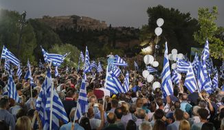 Supporter wave Greek flags as Greek opposition New Democracy party leader Kyriakos Mitsotakis, center, speaks during his main election campaign rally in Athens, in front of the ancient Acropolis hill, on Thursday, July 4, 2019. Greeks head to the polls in early general elections on Sunday, July 7. (AP Photo/Thanassis Stavrakis)