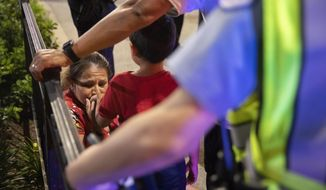 In this Thursday, July 4, 2019 photo, Chicago Police Department (CPD) officers stand guard while a woman relieves her son who had panicked after reports of stabbings and threatening injuries after the 4th of July celebrations at Chicago's Navy Pier.  Police said a false report of gunfire set off a stampede that trampled more than a dozen people.  (AP Photo/Amr Alfiky)