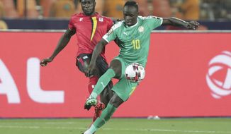 Uganda's Bevis Kristofer Kizito Mugabi, left, and Senegal's Sadio Mane fight for the ball during the African Cup of Nations round of 16 soccer match between Uganda and Senegal in Cairo International stadium in Cairo, Egypt, Friday, July 5, 2019. (AP Photo/Hassan Ammar)