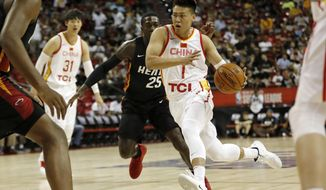 China's Zhao Rui (1) drives toward the basket past Miami Heat's Kendrick Nunn (25) during an NBA summer league basketball game Friday, July 5, 2019, in Las Vegas. (AP Photo/Steve Marcus)