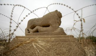 FILE - In this Sunday, May 6, 2012 file photo, barbed wire surrounds the Lion of Babylon at the archaeological site of Babylon. Iraq. Iraq is celebrating UNESCO's World Heritage Committee's naming the historic city of Babylon a World Heritage Site in a vote in Azerbaijan. Friday, July 5, 2019 vote comes after Iraq bid for years for Babylon to become a World Heritage Site. (AP Photo/Khalid Mohammed, File)