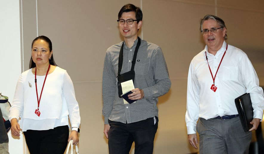 Australian student Alek Sigley, center, is escorted as he arrives at the airport in Tokyo on Thursday, July 4, 2019. The Australian student who vanished in North Korea more than a week ago arrived in Tokyo Thursday, July 4, 2019. (AP Photo/Eugene Hoshiko)
