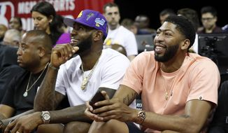 Los Angeles Laker players LeBron James, center, and Anthony Davis, right, take in an NBA summer league basketball game between the New York Knicks and the New Orleans Pelicans, Friday, July 5, 2019, in Las Vegas. (AP Photo/Steve Marcus)