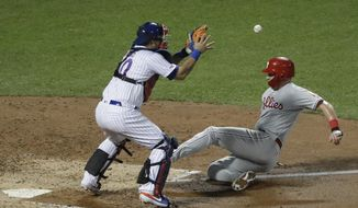 Philadelphia Phillies' Rhys Hoskins, right, slides past New York Mets catcher Wilson Ramos to score on a single by Cesar Hernandez during the seventh inning of a baseball game Friday, July 5, 2019, in New York. (AP Photo/Frank Franklin II)