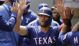 FILE - In this May 29, 2019, file photo, Texas Rangers' Hunter Pence is greeted in the dugout after he scored on an RBI single hit by Asdrubal Cabrera during the first inning of a baseball game in Seattle. Pence was being wished well in retirement last year.  Next week, he'll be at the All-Star Game representing the Rangers. (AP Photo/Ted S. Warren, File)
