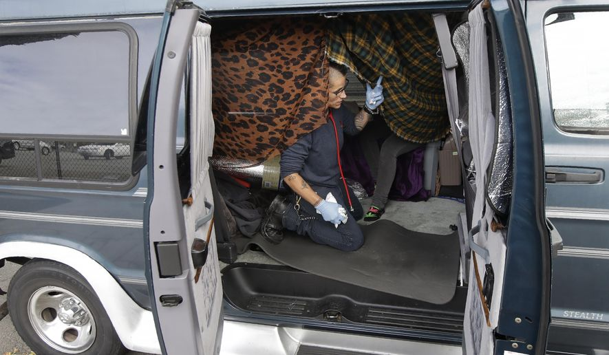 This Thursday, June 27, 2019, photo shows Shanna Couper Orona tending to her friend Jess (last name not given) in Jess' parked van along a street in San Francisco. A federally mandated count of homeless in San Francisco increased 17% in two years, driven in part by a surge of people living in RVs and other vehicles. (AP Photo/Jeff Chiu)