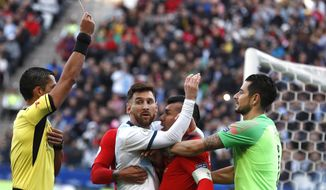 Argentina's Lionel Messi, center left, and Chile's Gary Medel, center right, scuffle as referee Mario Diaz, from Paraguay, left, shows the red card to both of them during Copa America third-place soccer match at the Arena Corinthians in Sao Paulo, Brazil, Saturday, July 6, 2019. (AP Photo/Victor R. Caivano)