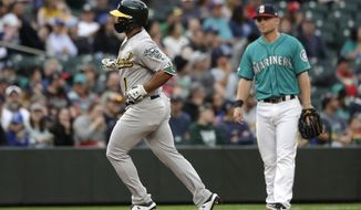 Oakland Athletics' Franklin Barreto (1) runs past Seattle Mariners third baseman Kyle Seager on Barreto's solo home run during the third inning of a baseball game Friday, July 5, 2019, in Seattle. (AP Photo/Elaine Thompson)