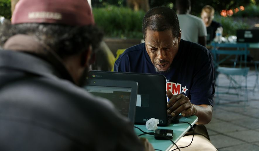 In this Monday, June 17, 2019 photo, Tony Rice uses a laptop at the Library on the Lawn in Woodruff Park, in Atlanta. Rice uses these computers to research or fill out applications while the Central Library is closed for renovations. (AP Photo/Andrea Smith)