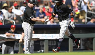 Miami Marlins' Starlin Castro, right, is congratulated by coach Fredi Gonzalez, left, as he rounds third base during his home run in the third inning of a baseball game against the Atlanta Braves, Saturday, July 6, 2019, in Atlanta. (AP Photo/John Amis)