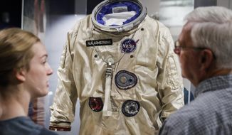 Visitors stand before the spacesuit worm by astronaut Neil Armstrong that was used on his Gemini VIII mission at the Armstrong Air & Space Museum, Wednesday, June 26, 2019, in Wapakoneta, Ohio.  Neil Armstrong helped put Wapakoneta  on the map July 20, 1969, when he became the first human to walk on the moon. The late astronaut remains larger than life in the city 60 miles (96.56 kilometers) north of Dayton, where visitors are greeted by the space base-shaped top of the space museum named for him as they exit Interstate 75.  (AP Photo/John Minchillo)