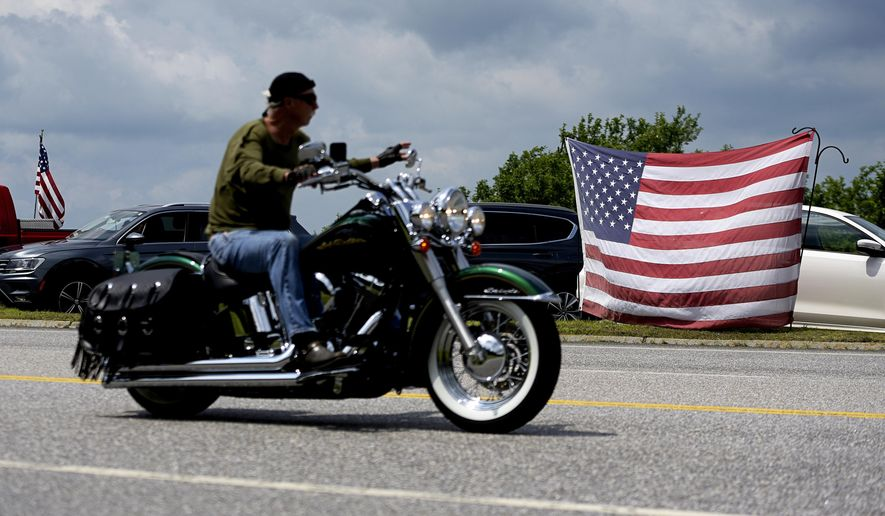 A motorcyclist passes an American flag on the route for the Ride for the Fallen 7 in near Randolph, N.H., on Saturday, July 6, 2019. Thousands of motorcyclists traveled through parts of New Hampshire as a tribute to the seven bikers killed in a collision with a pickup truck last month. (Paul Hayes/Caledonian-Record via AP)