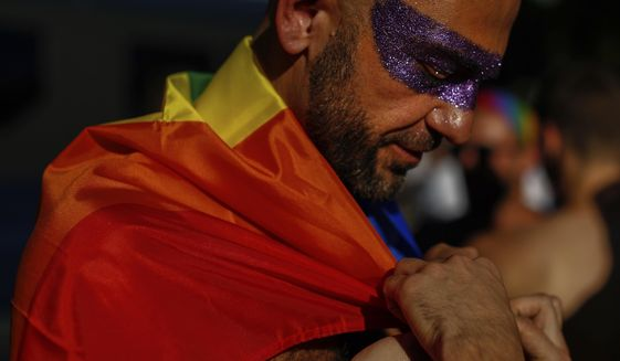 A reveller adjusts the rainbow flag during the LGBTQ pride parade in Madrid, Spain, Saturday, July 6, 2019. (AP Photo/Manu Fernandez)  ** FILE **