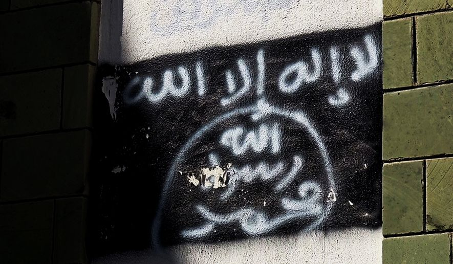 The black al-Qaida flag is sprayed on the wall of a damaged school that was turned into a religious court, in Taiz, Yemen, shown in this Oct. 16, 2017, photo. Al-Qaida fighters and other militants poured into Taiz to help defend it against Shiite rebels who have besieged it since 2015, and now the extremists are intertwined with militias financed by the U.S.-backed coalition. (AP Photo)